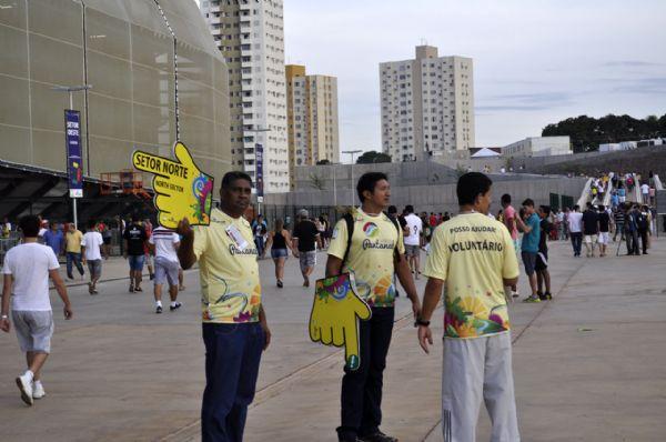 Trabalho de voluntários à frente da Arena Pantanal, em Cuiabá, em dia de jogo-teste