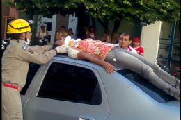 A mulher sendo atendida pelos bombeiros em cima do carro