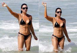 Luiza Brunet vai à praia  e faz gesto obsceno e poses para fotógrafo