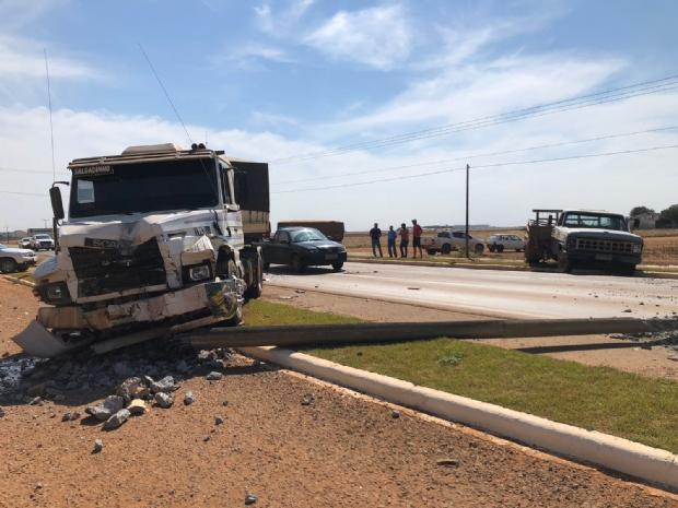 Casal e criança ficam feridos após carreta colidir com caminhonete; poste é derrubado