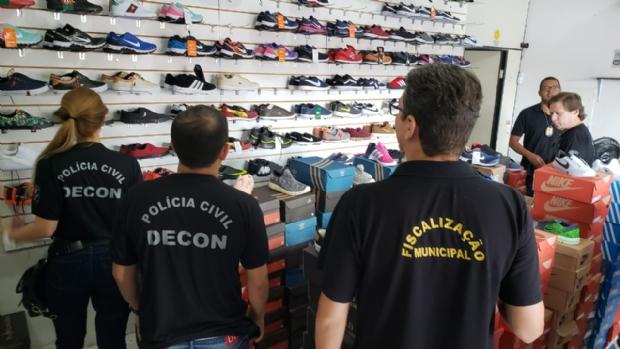 Ação conjunta apreende 300 pares de tênis e bonés falsificados em loja de Cuiabá