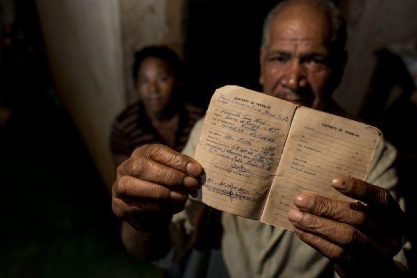 João Guarda, ao lado da esposa, mostra carteira de trabalho com registro da antiga fazenda Suiá Missú