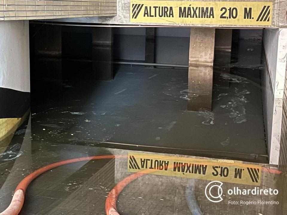 Nível da água em prédio alagado no Centro chega a 1,60m e bomba utilizada para escoar líquido foi roubada; vídeos e fotos