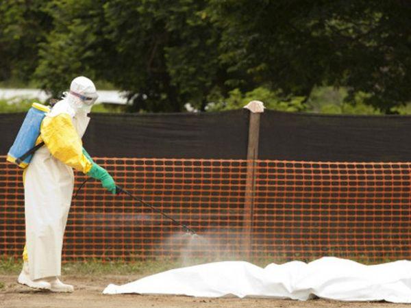 Funcionários desinfetam corpo de vítima do ebola na Libéria: governo tem sido criticado por resposta a surto