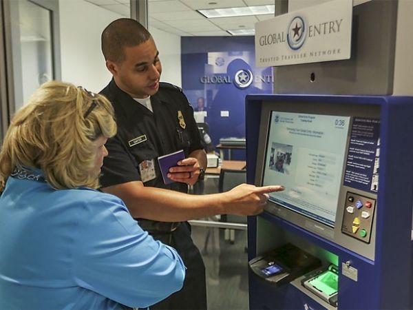 Funcionário da imigração americana explica uso da máquina do sistema Global Entry a usuária
