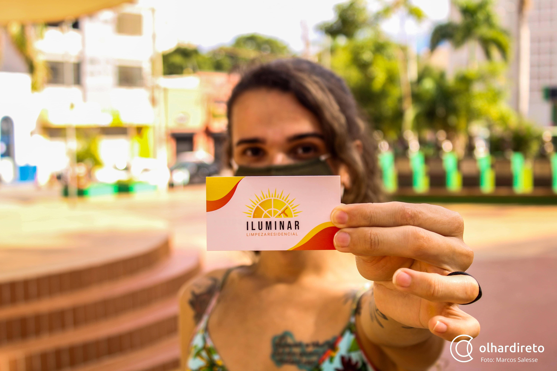 Sol segurando o cartão de visita da Iluminar Limpeza.